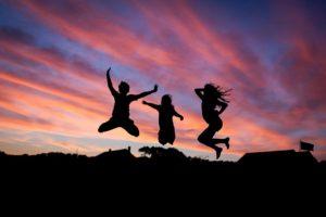 夕焼けの中でジャンプする健康的な若者たちのシルエット